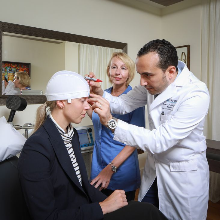 Dr Abdelghani taking personalised measurements to ensure precision of the TMS treatment